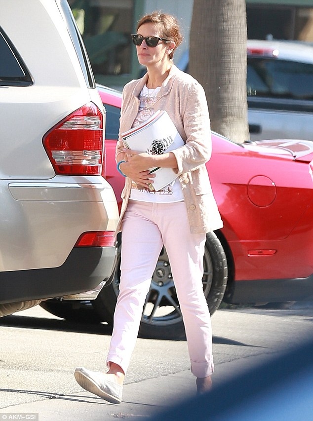 Pretty woman: Julia Roberts dons pink as she stocks up on magazines with husband Danny Moder in Malibu, California on Wednesday
