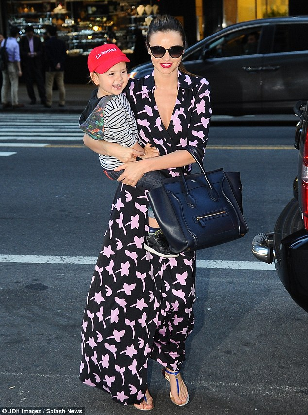 Reason to smile: Miranda Kerr cradled her happy boy Flynn as she ran errands in New York City on Wednesday