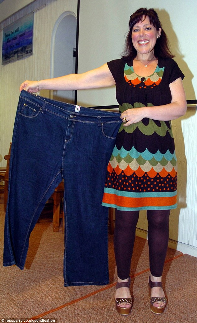 Marcia, who now weighs a slim 11st 2lbs, pictured after her weight loss now holding up a pair of the old jeans she no longer fits into