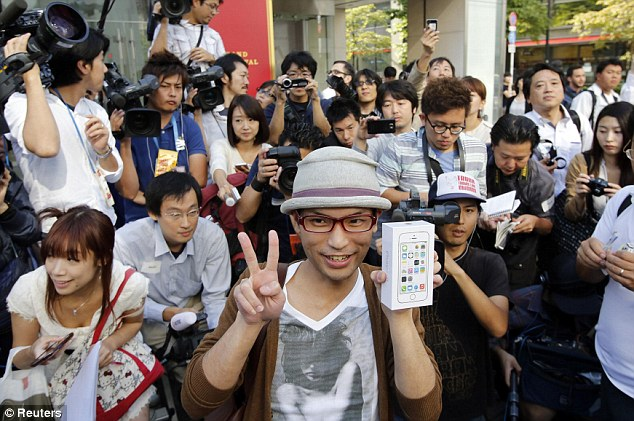 Superfan: An Apple fan poses with his new iPhone 5S  after queuing outside Apple's store at Tokyo's Ginza shopping district since September 10