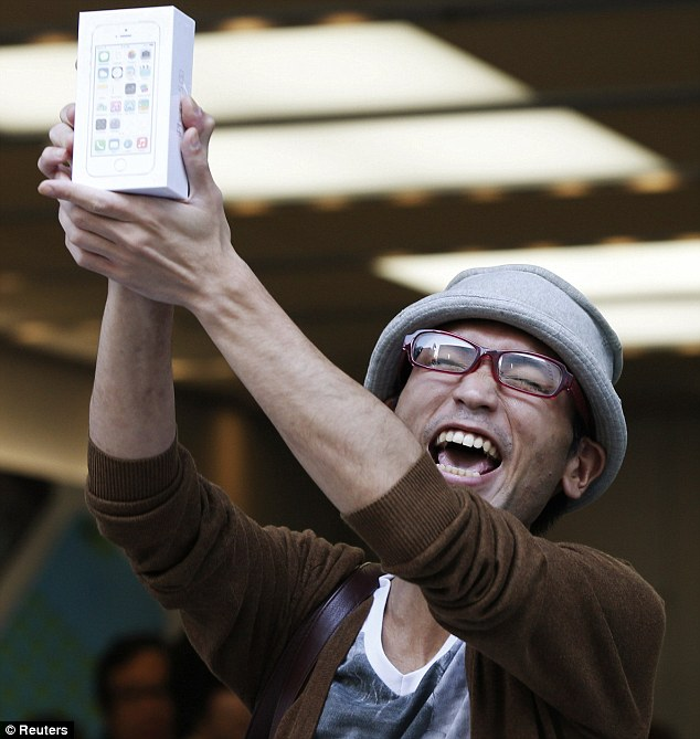 First in line: The first customer to purchase an iPhone 5S in Tokyo celebrates as he leaves an Apple store in the city's Store Ginza shopping district