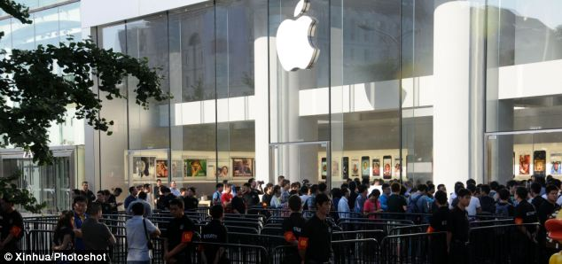 Customers line up to buy the latest Apple smart phones outside an Apple Store at Xidan Street in Beijing. It is the first time Apple has made the handsets available from launch in China as it attempts to reach emerging markets