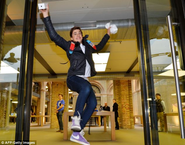 Jesse Green from London jumps as he leaves with his iPhone 5S after being the second person to enter the Apple store in Covent Garden