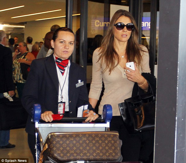 Missing each other: Elizabeth Hurley jets into New York on Thursday night - as her estranged fiance Shane Warne flies to England from Australia to try and win her back