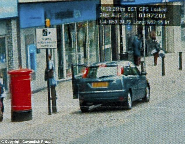 Stopped: Mr Hardman's car is pictured pulling over on Bolton high street at 14.22.28