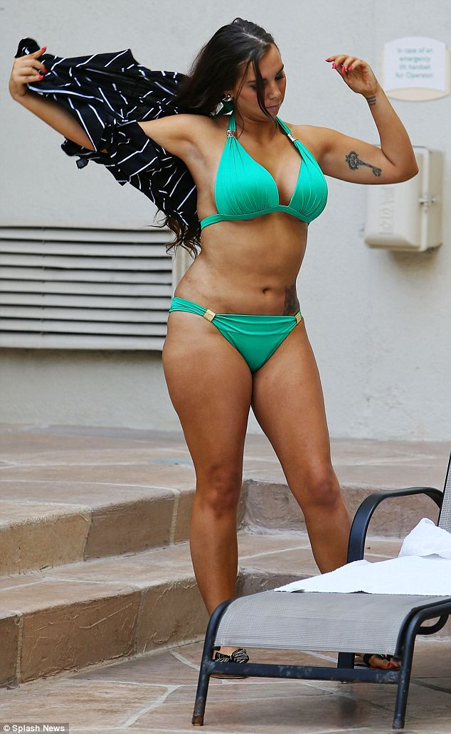 Starting out for the day: Leathers disrobes as she arrives poolside, showing off her surgically-enhanced curves in a green bikini