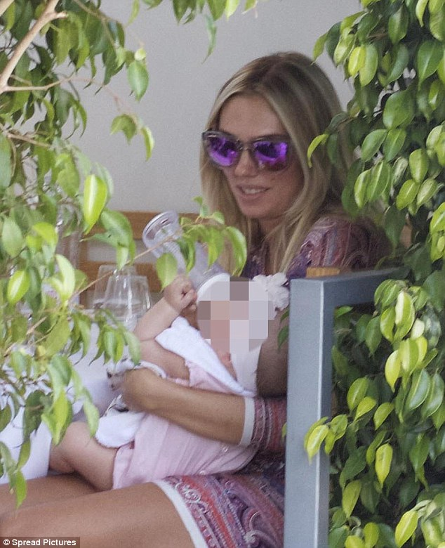 Liquid lunch: The glamorous mother gives her baby a bottle in Los Angeles