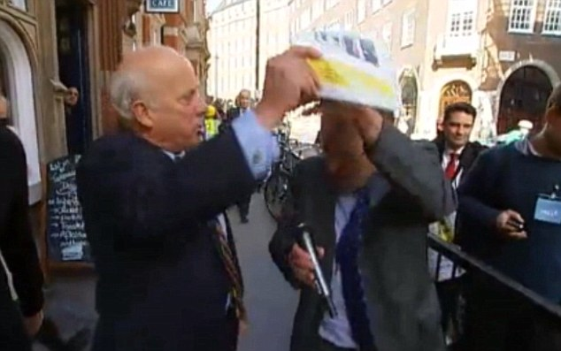 Clobber: Mr Bloom hit Mr Crick over the head with the UKIP brochure as they argued about the fact there were no white faces on the front cover