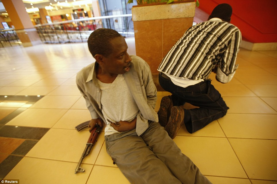 Wounded: A Kenyan policeman sits clutching his stomach alongside his rifle while a colleague exchanges fire with the terrorists