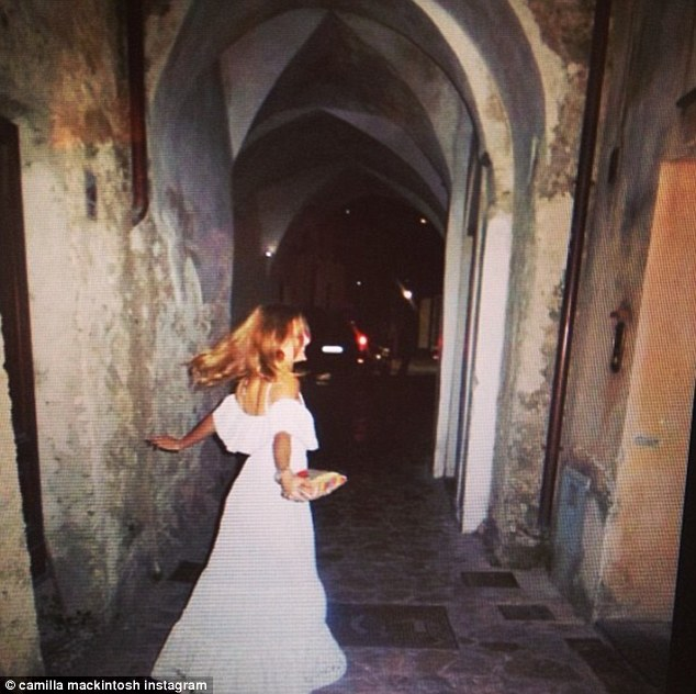 'Memories:' Millie tweeted a photo of herself running down some cobbled steps in a white maxi dress