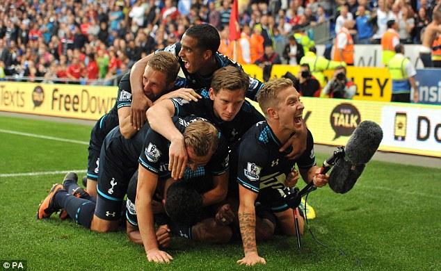 Left it late! Tottenham's players pile on goalscorer Paulinho