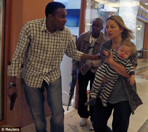 Terror: Armed police guide a woman carrying a child to safety at Westgate Shopping Centre