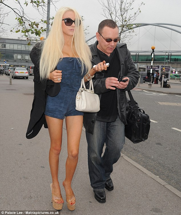Doug checks his messages while Courtney struts by his side outside Heathrow Airport on Monday
