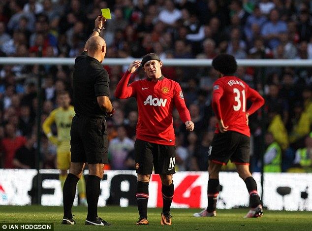 Cautioned: Howard Webb shows a yellow card to Wayne Rooney