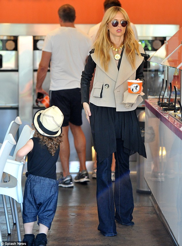 Topping up: The fashion icon perused the snack items as her boy played nearby
