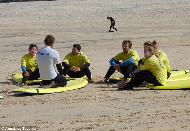 Calm before the storm: Surfers listen to instructor John before hitting the waves