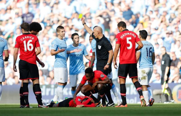 Man in the middle: City players complain to referee Howard Webb as he shows Matija Nastasic a yellow card