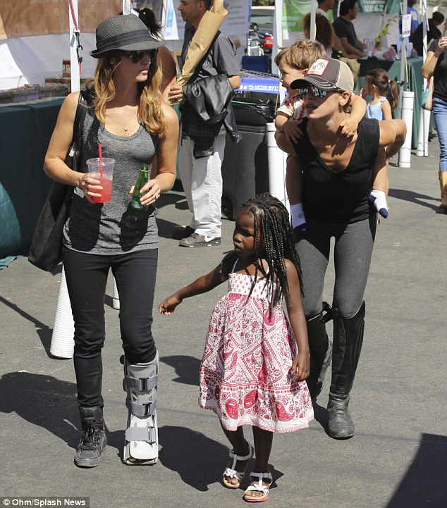 Staying fit: Jillian Michaels gave her toddler Phoenix a piggyback ride as she enjoyed a day at Malibu Farmers Market on Sunday with partner Heidi Rhoades and their daughter Lukensia