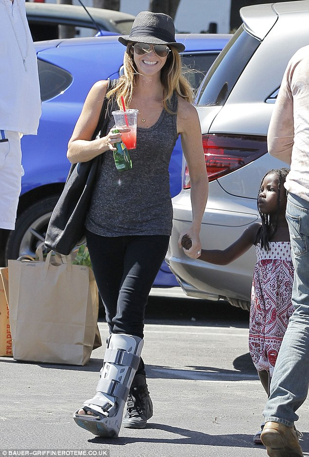 Hobbling along: Jillian's partner of four years sported a brace on her left foot as she led three-year-old Lukensia by the hand