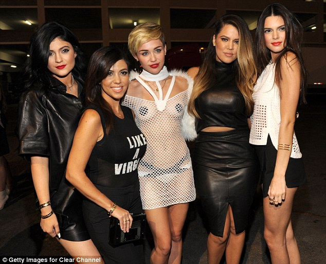 Smiling through the pain: Khloe with (from left) Kylie, Kourtney, Miley Cyrus, and Kendall at the iHeart Radio Music Festival