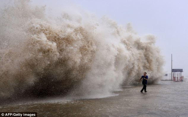 Running for cover: This photo shows a man running away from a huge wave pushed up by Typhoon Usagi on a wharf in Shantou, south China's Guangdong province