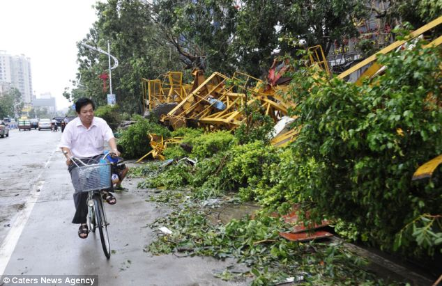 Devastation: A man rides a bike past a collapsed construction site in Shanwei City, south Chinas Guangdong Province
