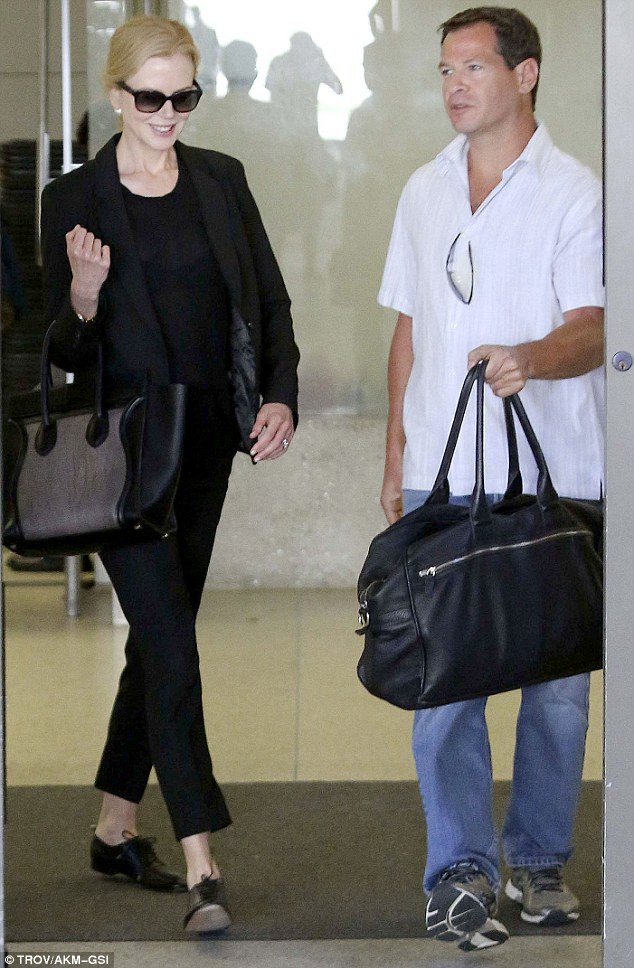Picked up: Nicole is clearly pleased to see a familiar face as she leaves arrivals at LAX for a waiting car