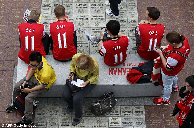 Hit with the fans: Arsenal fans wearing the No 11 shirt of new signing Ozil on the back