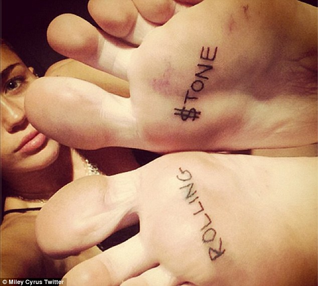 Permanent reminder: Miley tweeted this picture of her feet tattooed with the words 'Rolling $tone' to celebrate her big cover