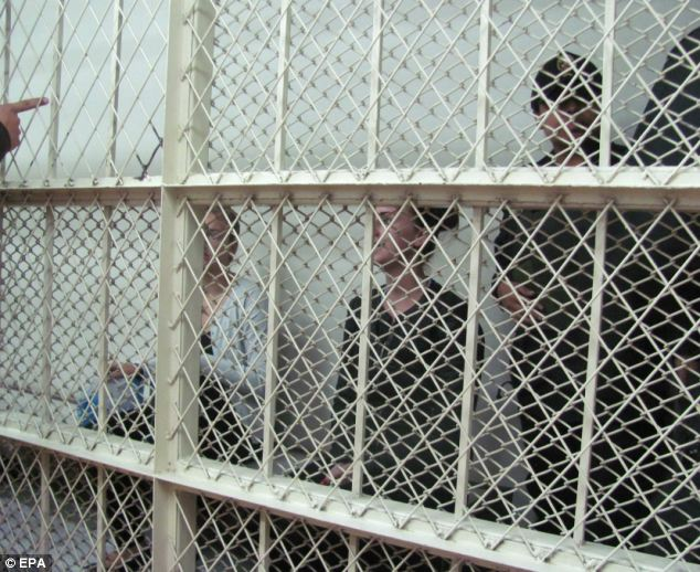 Behind bars: After the pair arrived at the court, they were detained in a holding cell, surrounded by guards, as they awaited their appearance in front of a judge