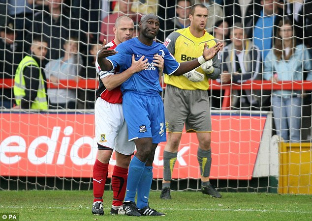 Morcambe's James Bentley gets to grips with Sol Campbell during the League Two match at Christie Park in September 2009