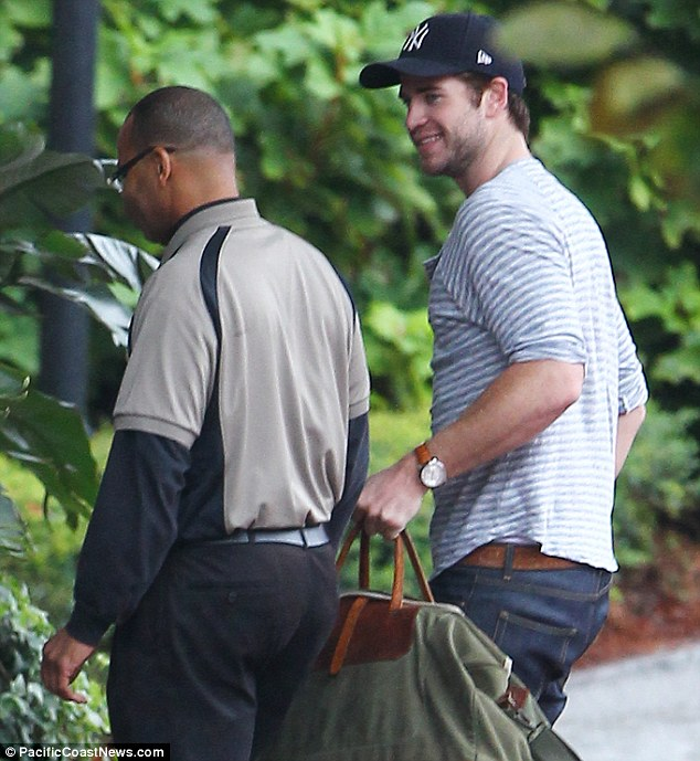 Liam Hemsworth was all smiles as he returned to Atlanta to film for Hunger Games this week