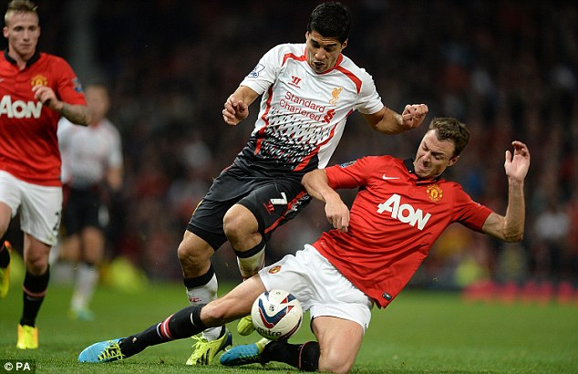 Getting stuck in: Suarez battles for the ball with Jonny Evans on his return to action for Liverpool