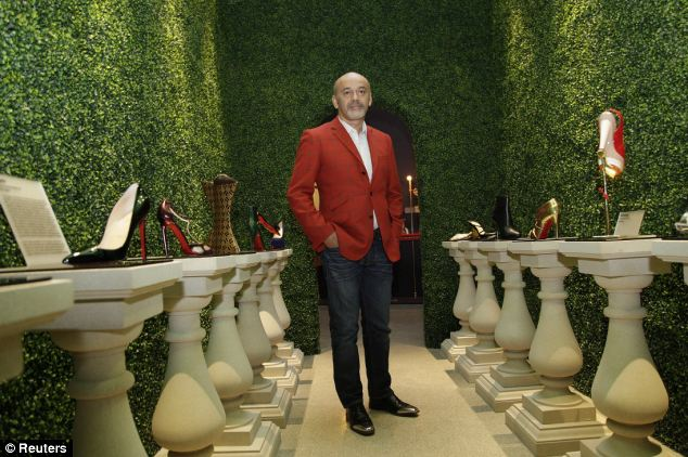 Action: Luxury shoe designer Christian Louboutin poses for photographs at the Design Museum in London
