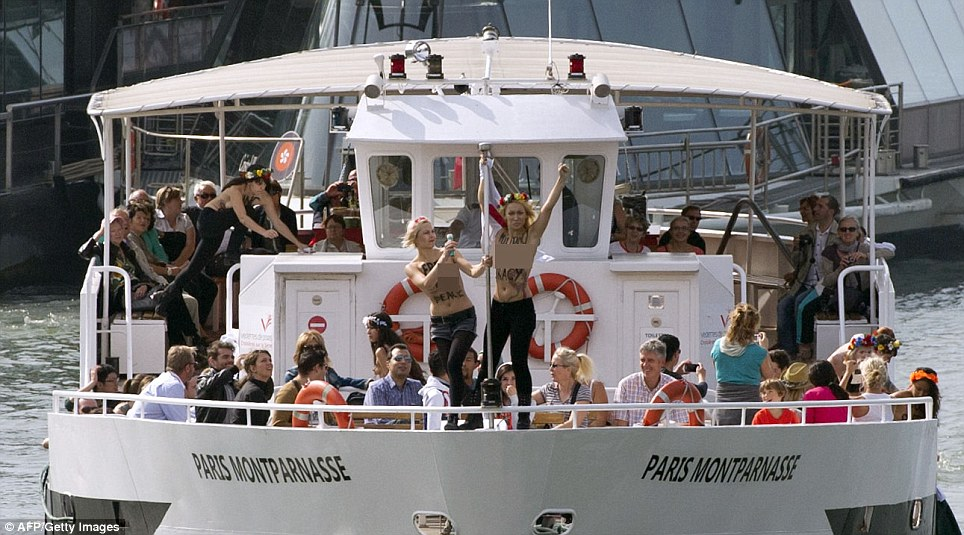 Baffled: Tourists enjoying the Parisian sunshine looked bemused as the Ukrainian activists ran topless around the boat daubed in slogans that read 'Hang Captain Putin'