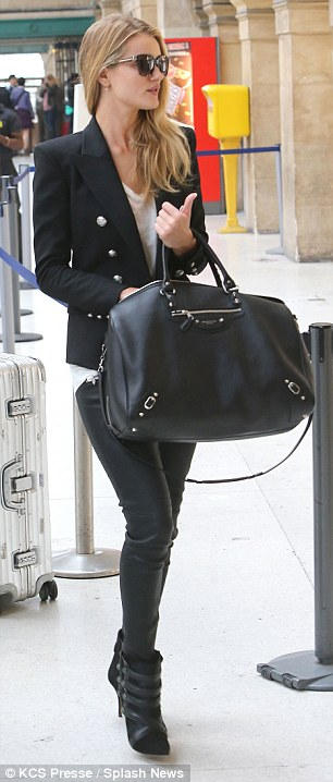 Travelling light: Rosie toted her designer bag which perfectly matched her black jackets and leather trim pants