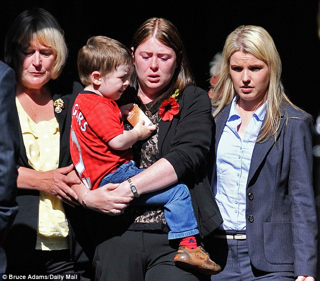 Distraught: Widow Rebecca Rigby, centre, holds son Jack, two, during the funeral of the Fusilier Lee Rigby at Bury Parish Church, Bury, Lancashire
