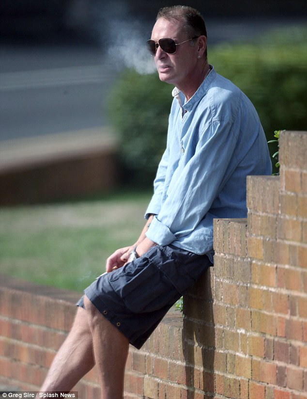 Break time: The former football star took a moment for himself while having a cigarette