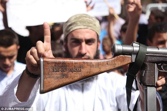 Spreading the word: An Al Qaeda Fighter shows his AK-47 machine gun with Arabic language professing allegiance to 'al-Qaeda' organization