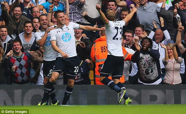 Main man: Sigurdsson peels away to celebrate with team-mates after opening the scoring at White Hart Lane