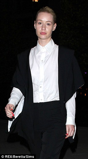 All covered up: Iggy Azalea covers up in a white shirt and black trouser suit at the Yohji Yamamoto show at Paris Fashion Week
