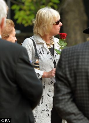 Carol Thatcher holds a red rose before placing it with the ashes of her mother