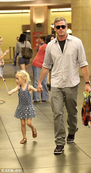Treats: Eric carries goodie bags while his daughter Billie dances around and enjoys the fun