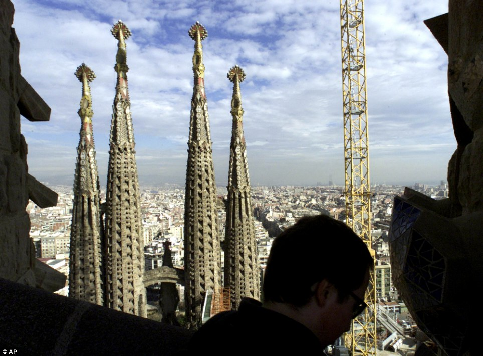 A tourist walks on a new tower of  La Sagrada Familia: While often referred to as a cathedral, and originally intended as such, La Sagrada Família was consecrated in November 2010 as a basilica by Pope Benedict XVI