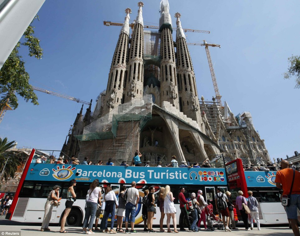 A city tour bus stands before the site: La Sagrada Família attracts around 3million visitors a year, whose entrance fees pay for most of the 25million euro a year cost of continuing its construction
