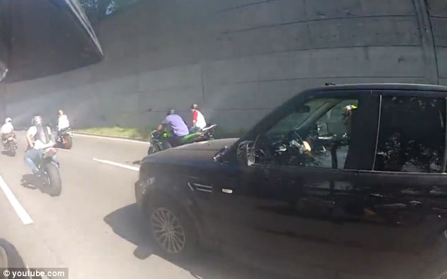 Fearful: The bikers had been riding alongside the Range Rover before the incident. Shortly after this moment, the biker in blue jeans - Christopher Cruz - braked