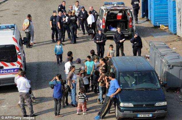 Camps: Roma people stand next to police as they carry out checks. Their treatment has sparked controversy across France