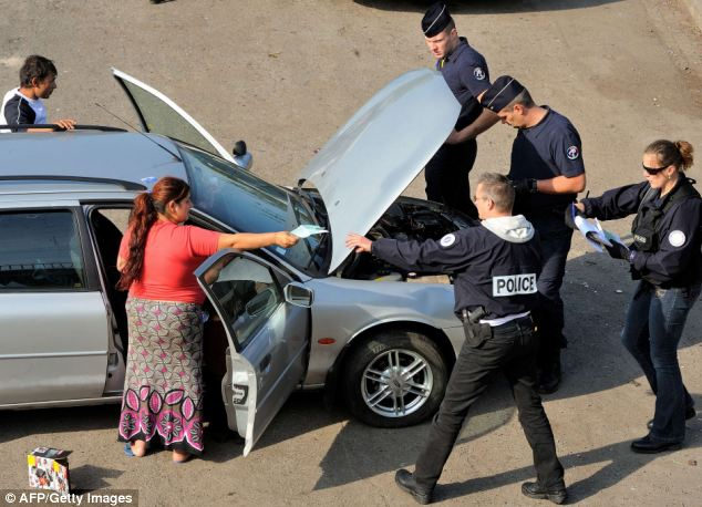 Inspection: A Roman woman hands over papers as officers carry out checks on her car