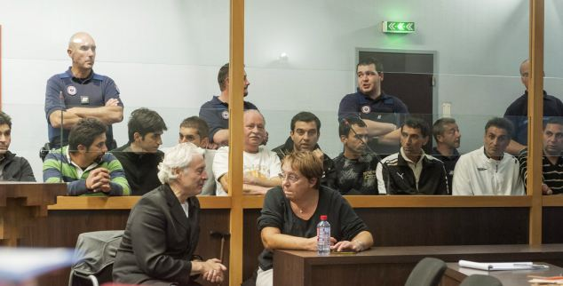 Shamed: The Roma gypsy gang currently facing trial sit behind glass in a courtroom in Nancy, France