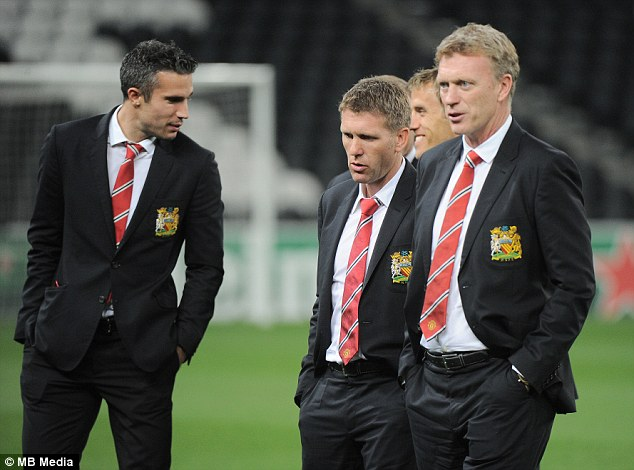 Suited and booted: David Moyes (right), with Steve Round and Robin van Persie (left) on the Donbass turf